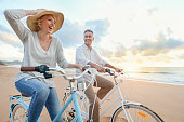 istock Mature couple cycling on the beach at sunset or sunrise. 959016450