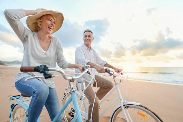 coppia matura in bicicletta sulla spiaggia al tramonto o all'alba. - ciclismo foto e immagini stock