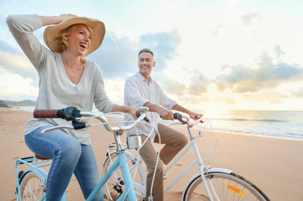 Mature couple cycling on the beach at sunset or sunrise. stock photo