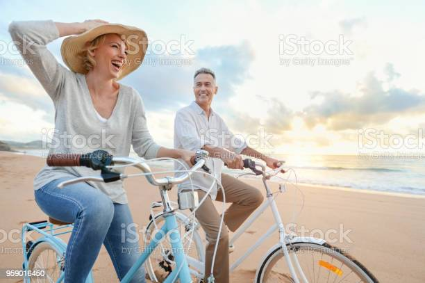 Photo of Mature couple cycling on the beach at sunset or sunrise.