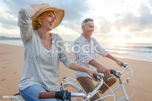 istock Mature couple cycling on the beach at sunset or sunrise. 959016452