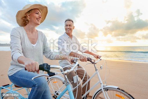 istock Mature couple cycling on the beach at sunset or sunrise. 959016454