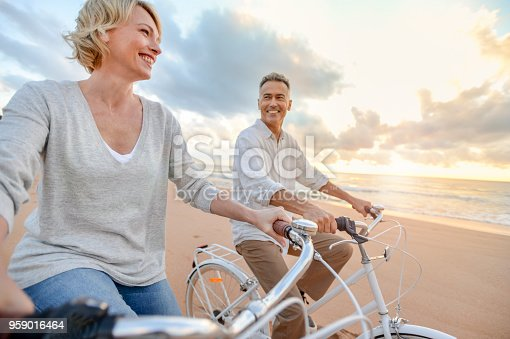 istock Mature couple cycling on the beach at sunset or sunrise 959016464
