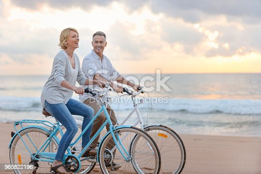 Mature couple cycling on the beach at sunset or sunrise. They are laughing and having fun. They are casually dressed. Could be a retirement vacation.