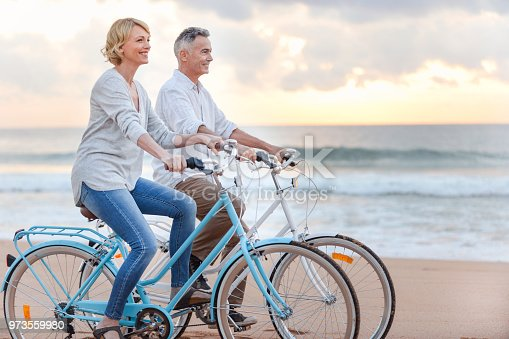 istock Mature couple cycling on the beach at sunset or sunrise. 973559980