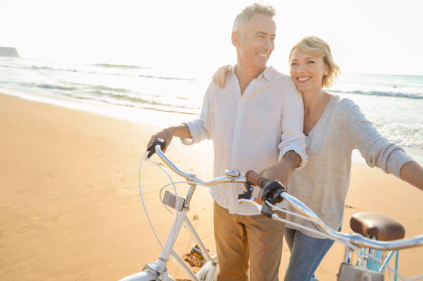 Mature couple cycling on the beach at sunset or sunrise Mature couple cycling on the beach at sunset or sunrise. The ocean is in the background. They are happy and smiling. They are standing beside their bicycles. They are casually dressed. Could be a romantic retirement vacation. mature couple stock pictures, royalty-free photos & images