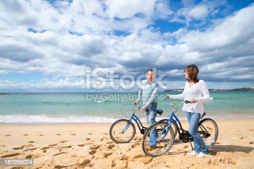 istock Mature couple cycling on the beach 187055024