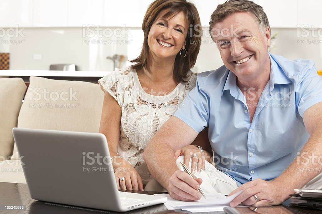Mature couple doing paperwork with laptop royalty-free stock photo