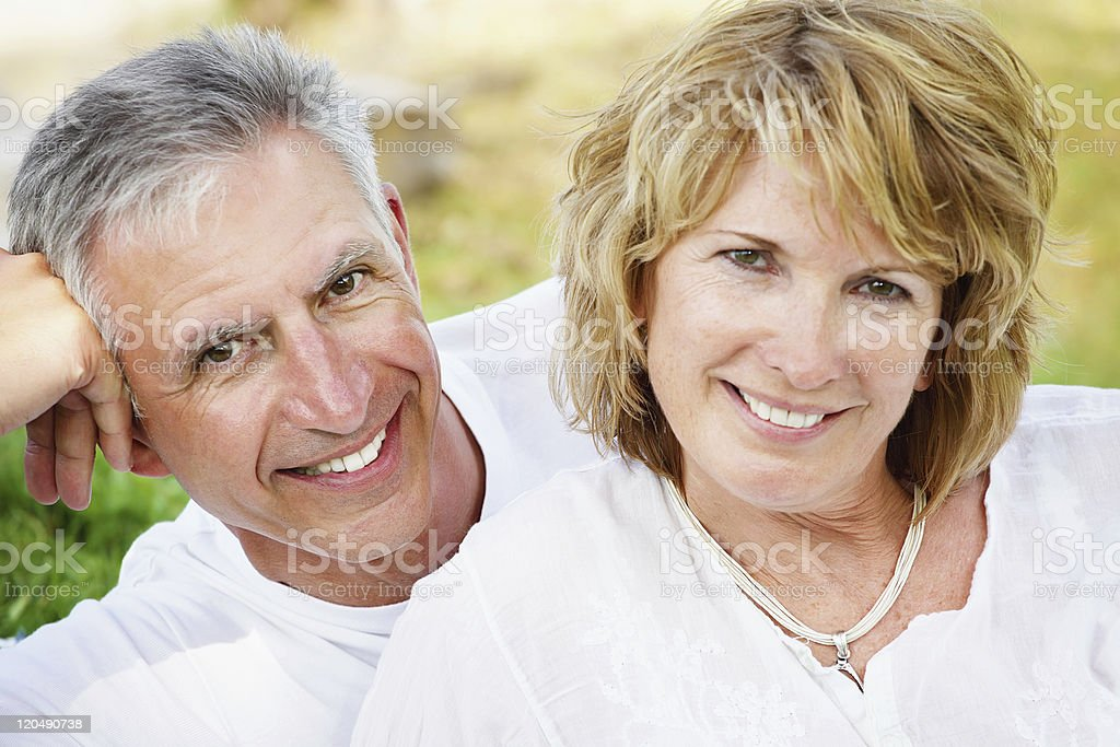 Mature couple dressed in white, smiling royalty-free stock photo