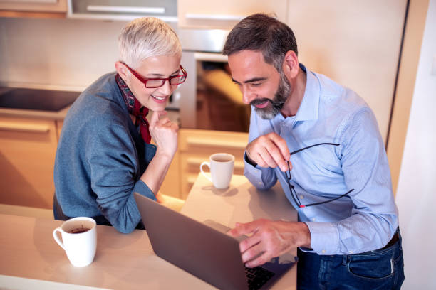 Mature couple drinking coffee and using laptop in the morning stock photo