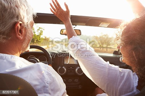 istock Mature Couple Driving Along Country Road In Open Top Car 522017301