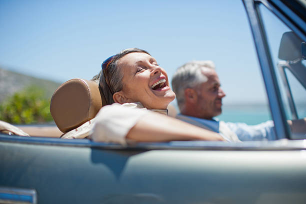 Mature couple driving in convertible stock photo