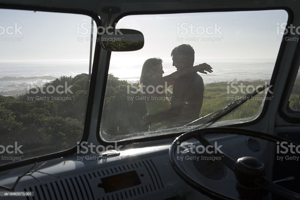 Mature couple embracing on field near beach, view through van windshield foto de stock libre de derechos