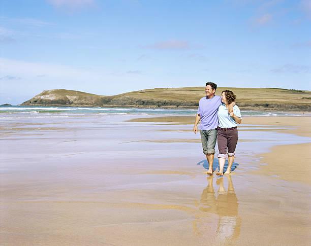 Mature couple embracing, walking on beach stock photo