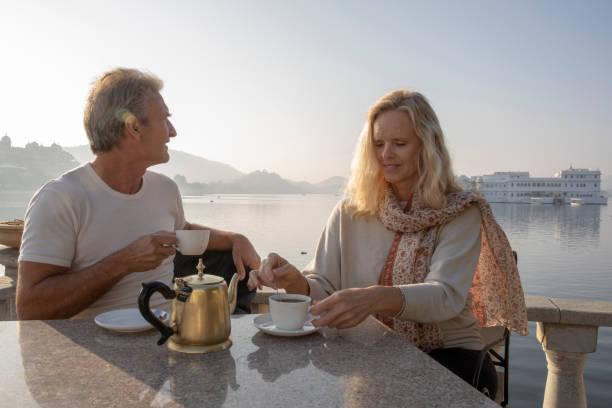Mature couple enjoy tea with lake and floating palace behind Lake Pichola, Udaipur lake palace stock pictures, royalty-free photos & images