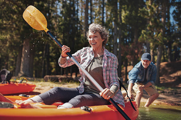mature couple enjoying a day at the lake with kayaking - aktiva pensionärer utflykt bildbanksfoton och bilder