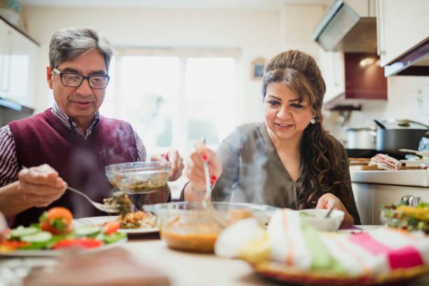 mature couple profitant de dîner à la maison - mariage musulman photos et images de collection