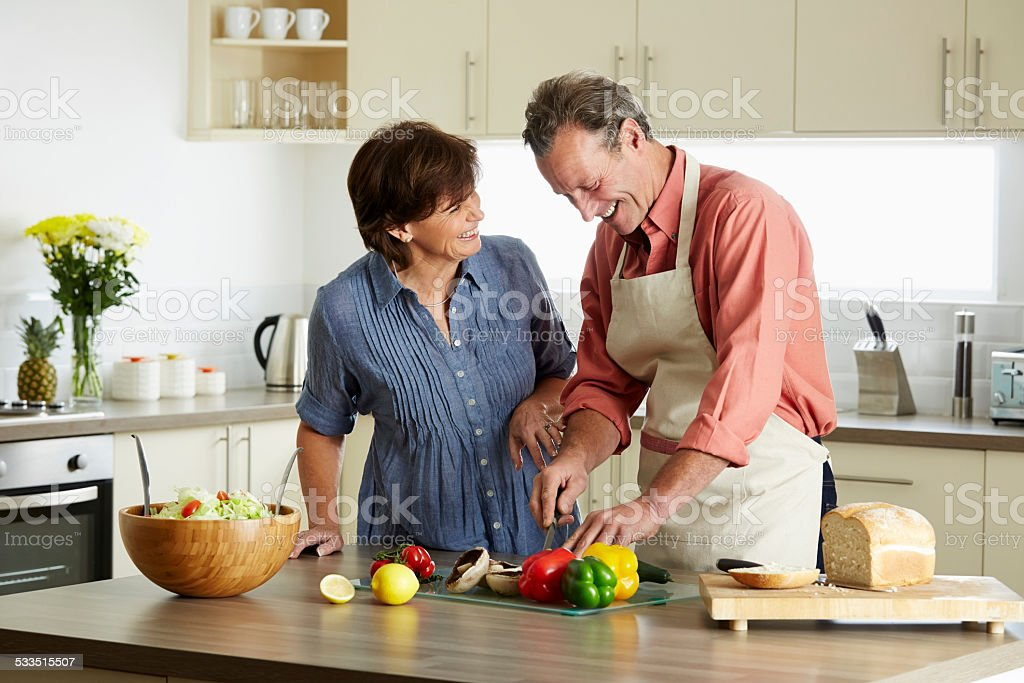 Mature couple enjoying making dinner together stock photo
