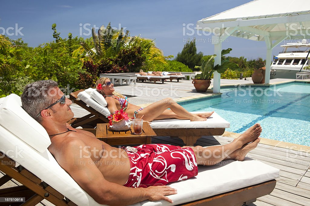 Mature couple enjoying relaxing vacation poolside at luxury resort royalty-free stock photo