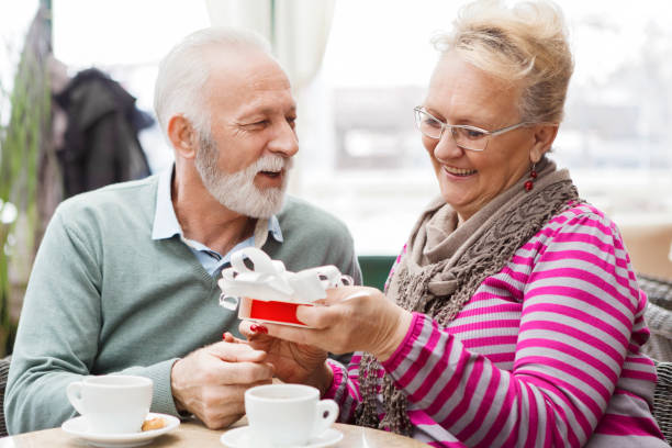 mature couple exchanging gifts - senior valentine stock photos and pictures