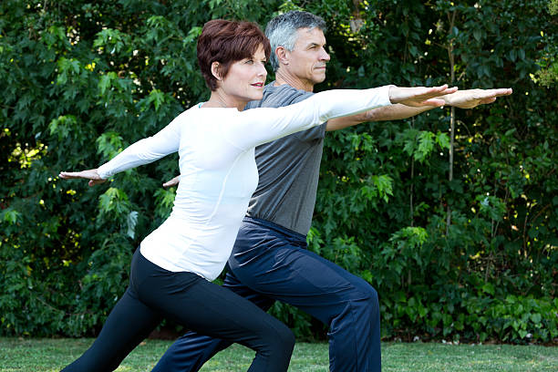 mature couple exercising outdoors stock photo