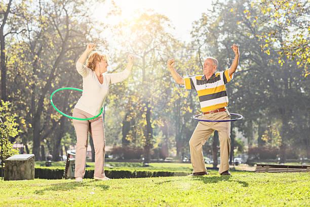 älteres paar ausübung im park mit hula-ringe - hula hoop workout stock-fotos und bilder