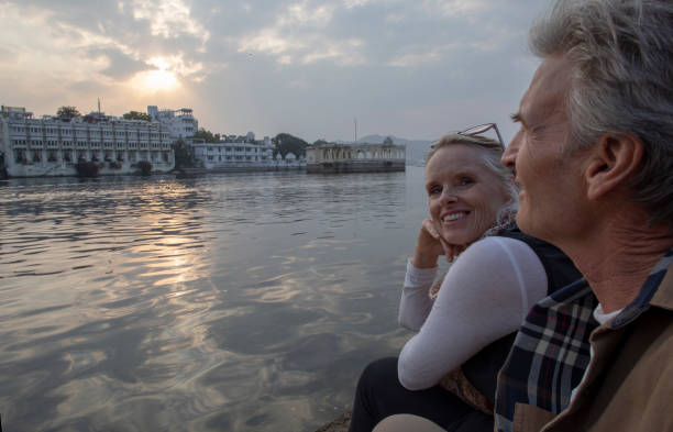 Mature couple explores a ghat at sunrise They look across water. Lake Pichola, Udaipur lake palace stock pictures, royalty-free photos & images