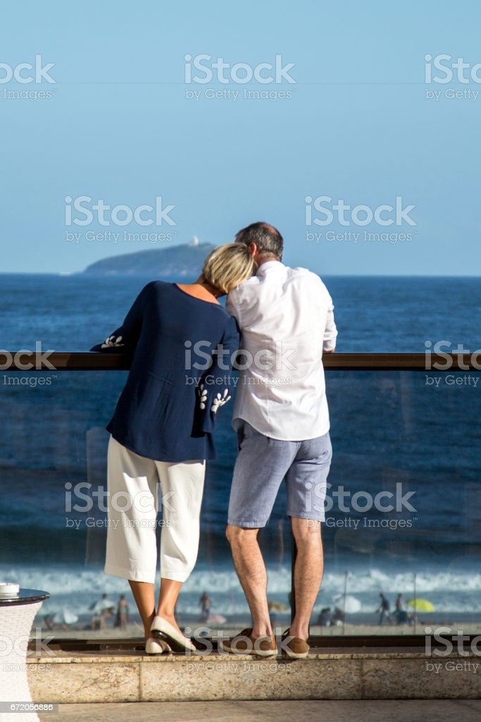 Mature couple from behind. Her head resting on his shoulder stock photo