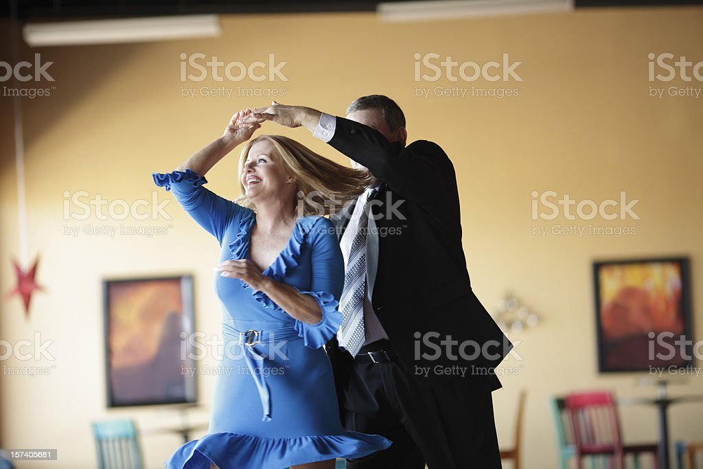 Mature couple happily ballroom dancing indoors stock photo