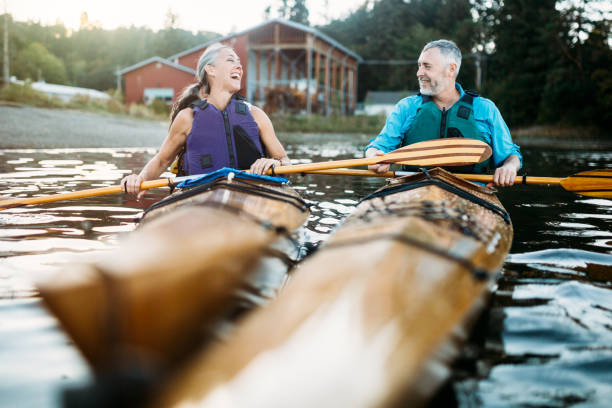 mature couple has fun kayaking - vitality stock photos and pictures