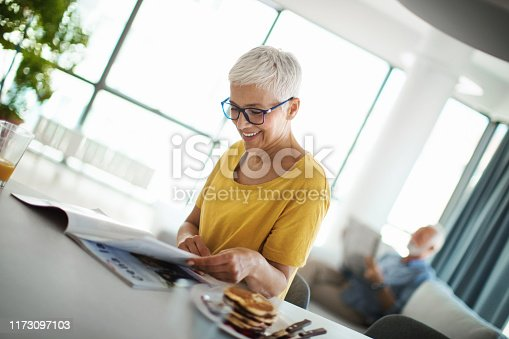 Closeup of a cheerful mid 60's couple having a morning coffee on a weekend morning. She's having orange juice and reading a magazine, while her husband is reading his daily newspapers on sofa in the background.