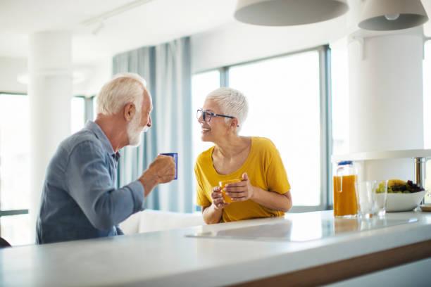 Reifes Paar mit einem Morgenkaffee an einer Küchentheke. – Foto