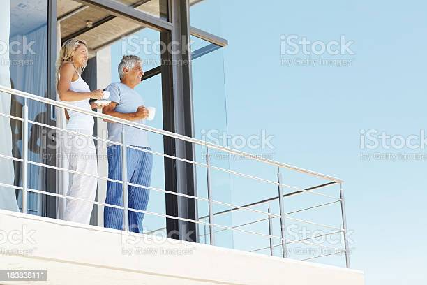 Mature Couple Having Coffee At The Balcony Stock Photo - Download Image Now