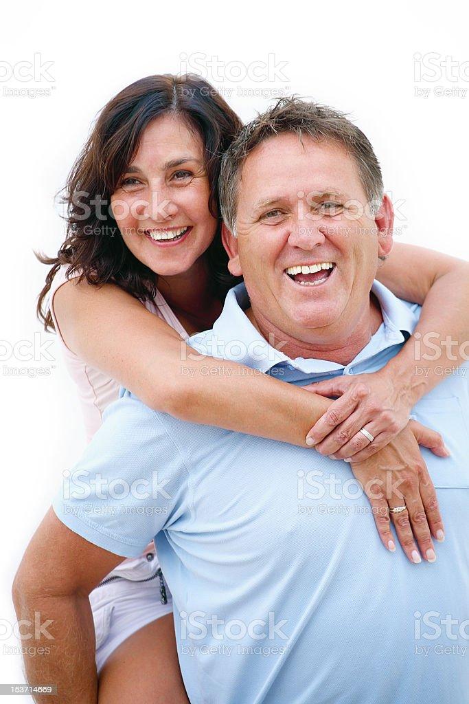 Mature couple having fun giving piggy back ride royalty-free stock photo