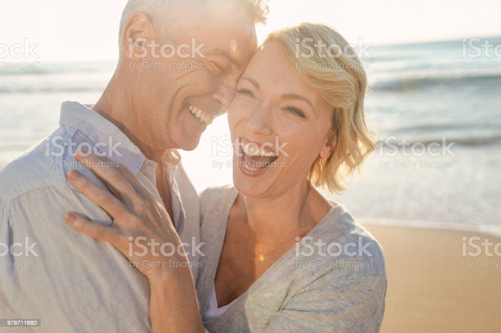 Mature couple having fun on the beach. stock photo