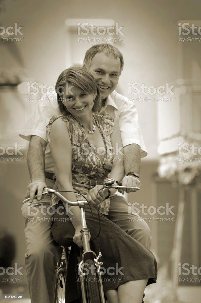 Mature Couple Having Fun Riding Bicycle, Sepia Toned royalty-free stock photo