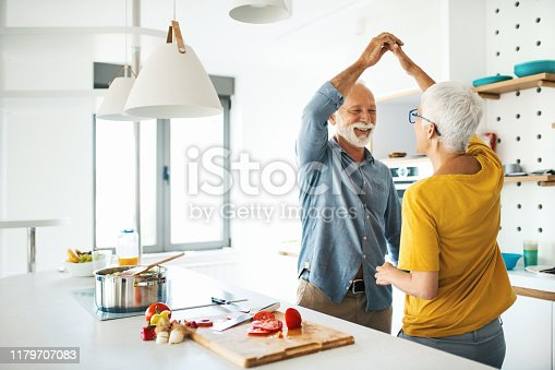 Closeup side view of a mid 60's couple having fun while cooking lunch together. They are dancing next to kitchen counter as the vegetable soup is slowly simmering.