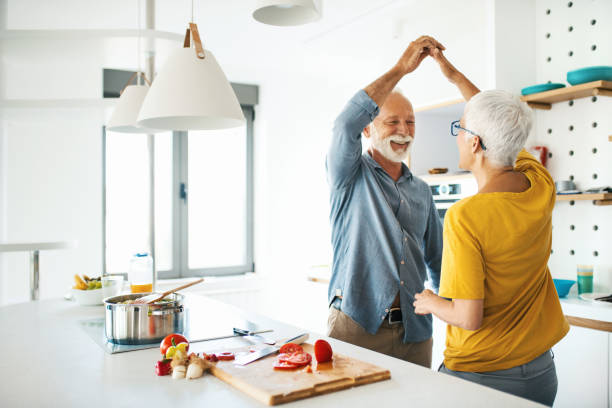 mature couple having fun while cooking lunch. - cooker happy imagens e fotografias de stock