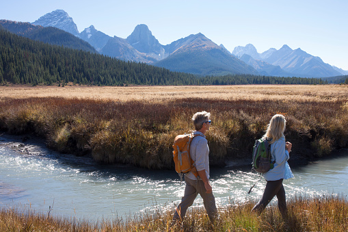 Mature couple hike through grassy riverbank in the morning