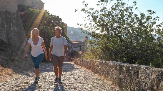 Mature couple hike up cobble stone path at sunrise