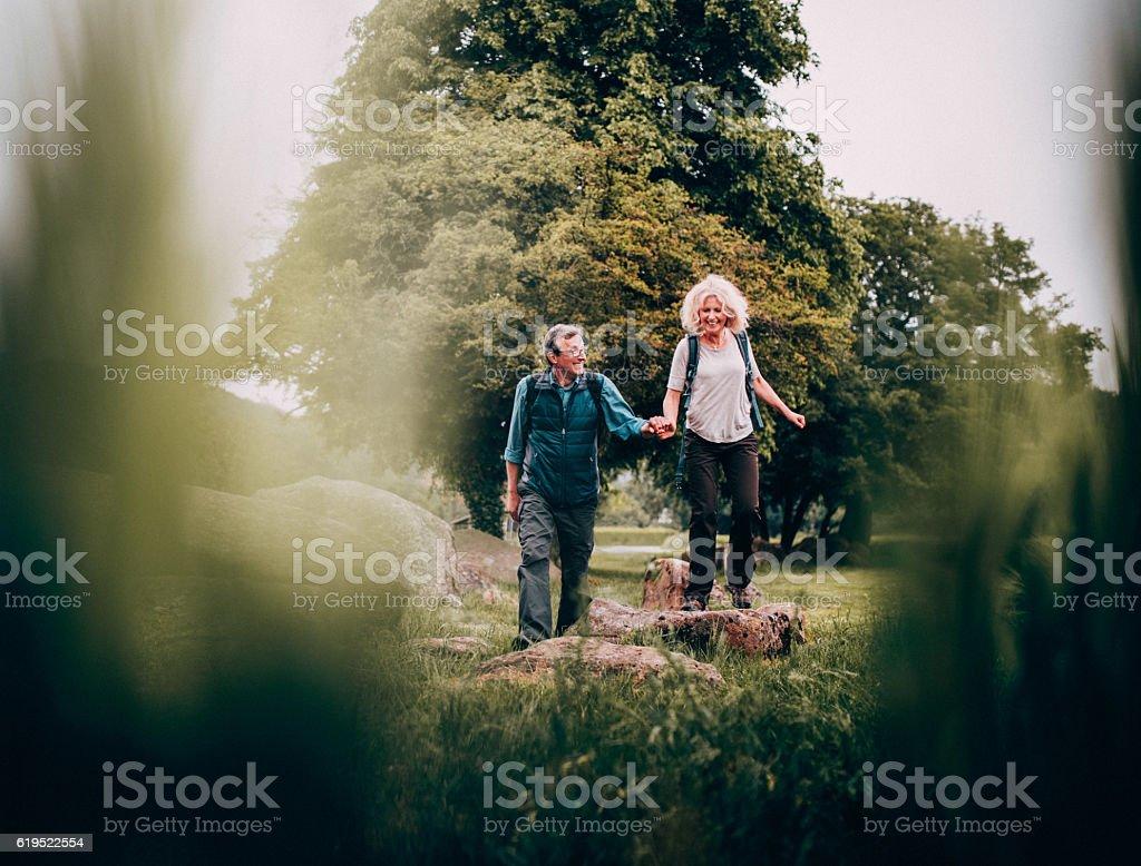 Mature Couple hiking trough beautiful green fields - foto de acervo