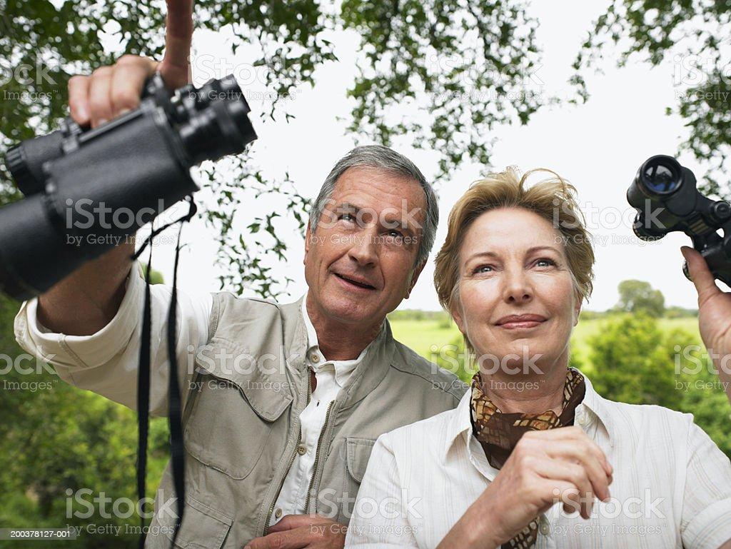 Mature couple holding binoculars, man pointing upwards, smiling stock photo