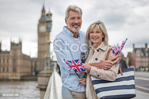 Portrait of mature couple holding British Flags. Smiling man and woman are standing on Westminster Bridge. They are against Big Ben.