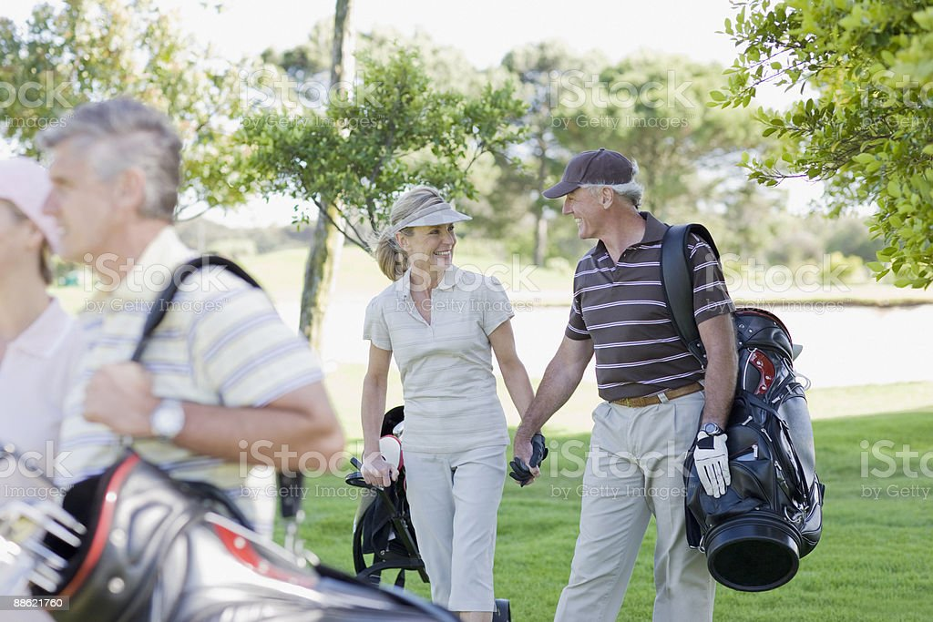 Mature couple holding hands and carrying golf bags royalty-free stock photo