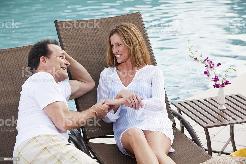 Mature couple holding hands by swimming pool royalty-free stock photo