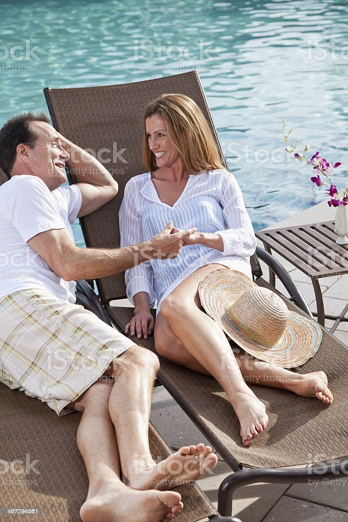 Mature couple holding hands by swimming pool stock photo