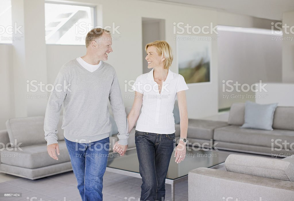 Mature couple holding hands in living room royalty-free stock photo