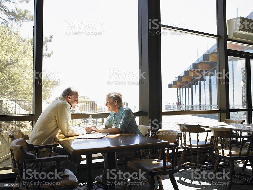 Coppia matura con le mani in ristorante foto stock royalty-free