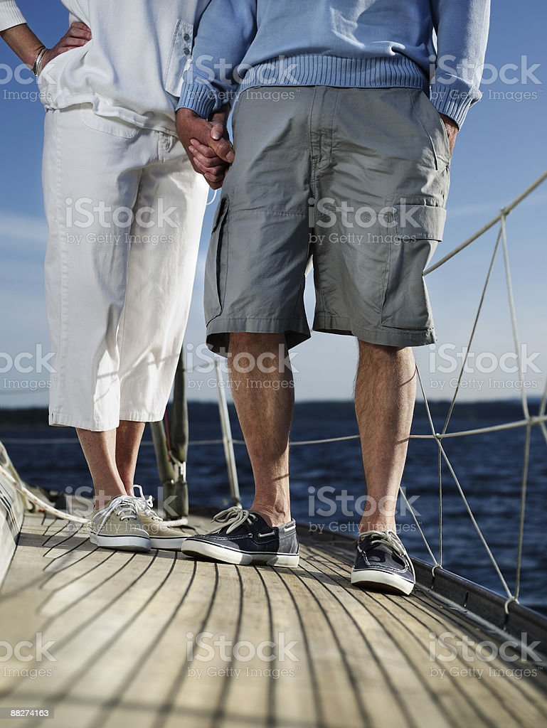 Mature couple holding hands on sailboat royalty-free stock photo