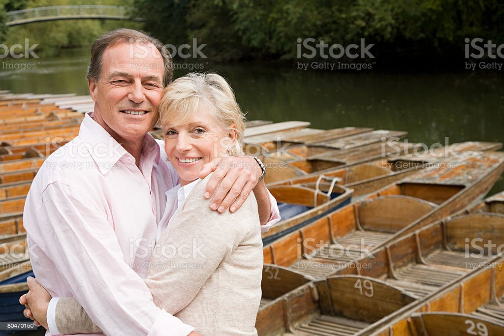성숙한 커플입니다 껴안기 rowboats 근처 royalty-free 스톡 사진